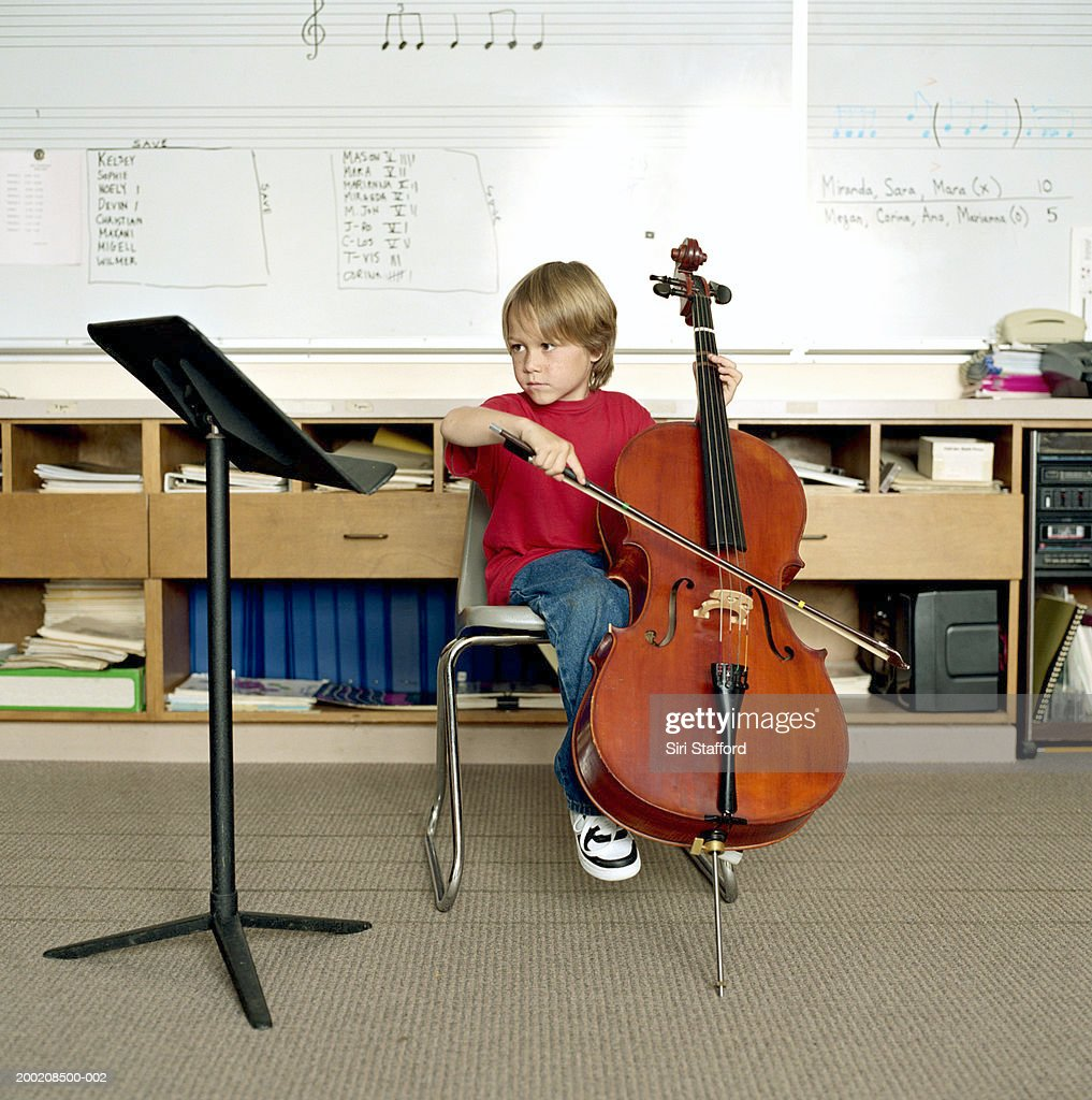 Boy (5-7) playing cello in classroom : Stock Photo