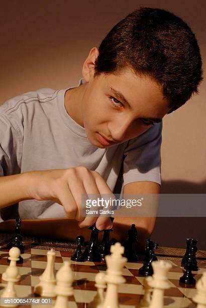 Boy (13-14) playing chess, portrait