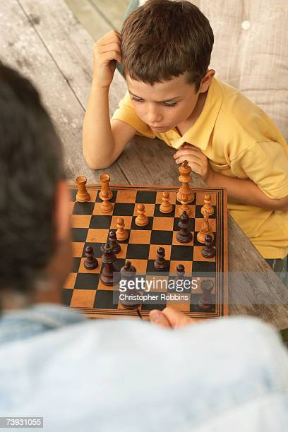Boy (8-9) playing chess with father, elevated view