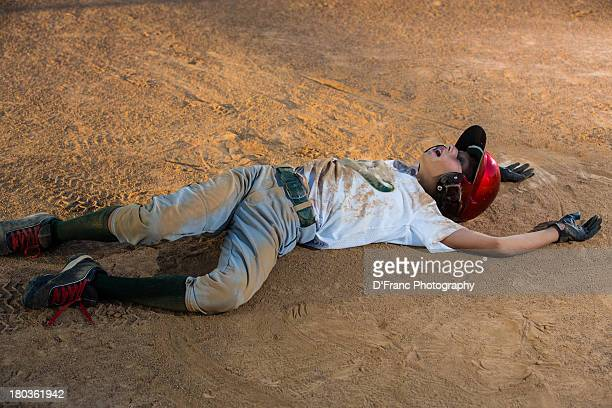 boy playing dead at home plate