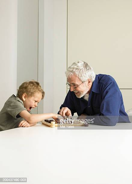 Boy (5-7) playing draughts with grandfather