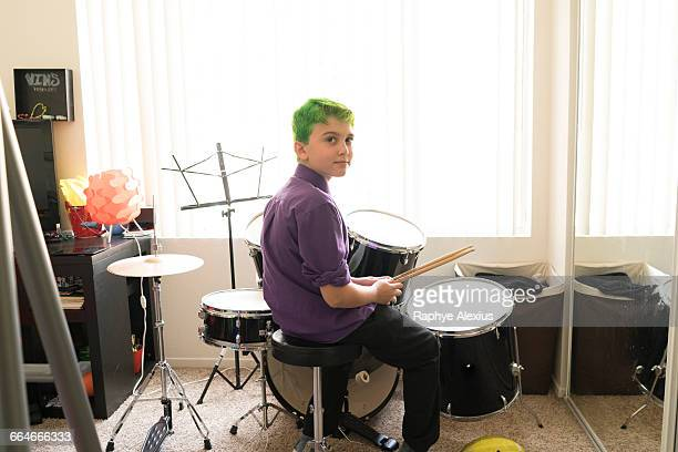 Boy playing drums in bedroom
