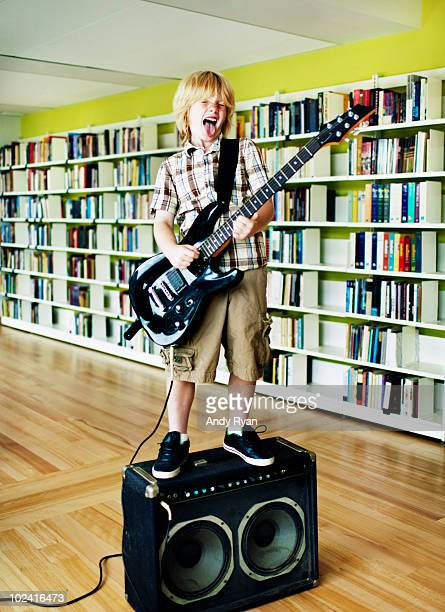 boy playing electric guitar in library