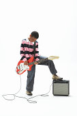 Boy (9-11) playing electric guitar, resting foot on amplifier