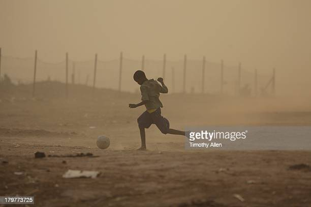 Boy playing football in dust storm, Djenne, Mali