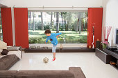 Boy (8-9) playing football in living room