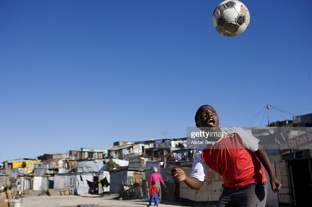 Boy playing football in South African township : Stock Photo