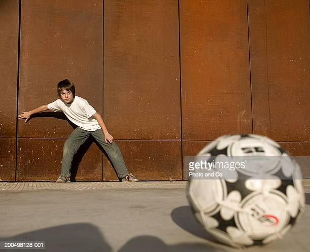 Boy (10-11) playing football in street