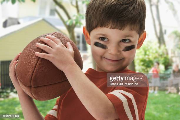 Boy playing football outdoors