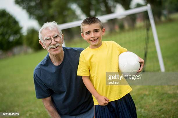 Boy playing football with his coach