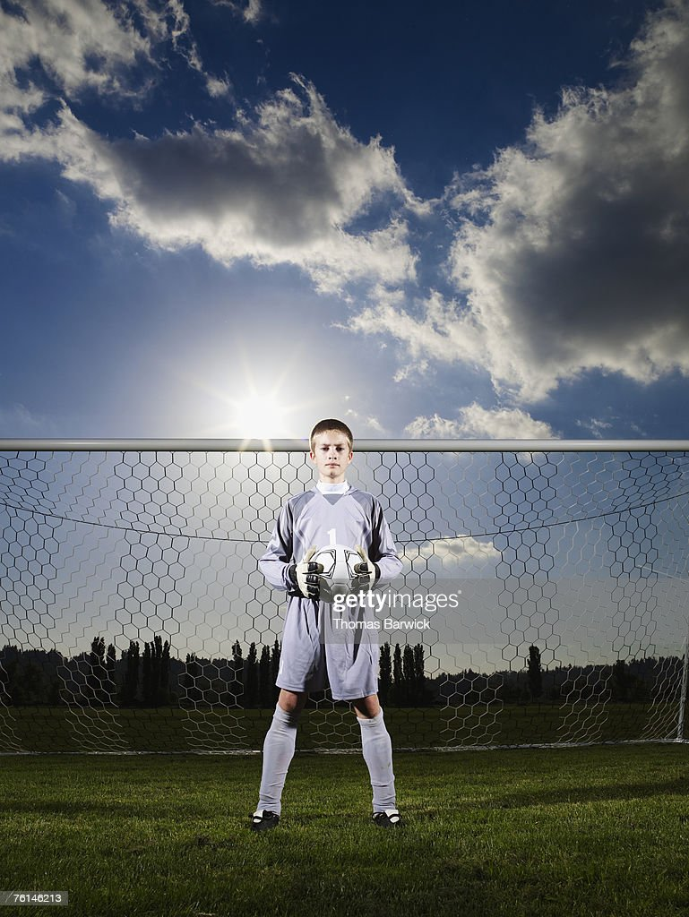 Boy (12-13) playing goaltender, holding football in front of goal : Stock Photo