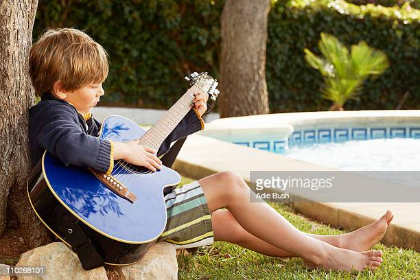Boy playing guitar by pool