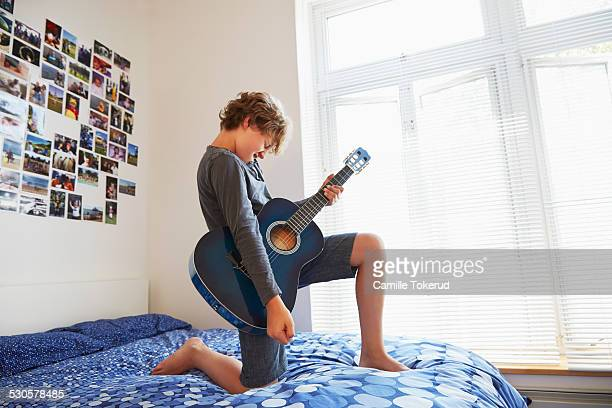 Boy playing guitar in his room
