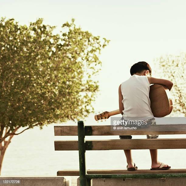 Boy playing guitar in seaside,
