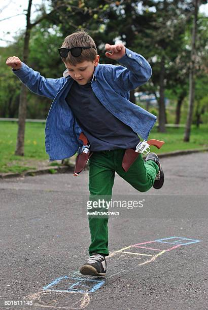 Boy playing hopscotch on the street