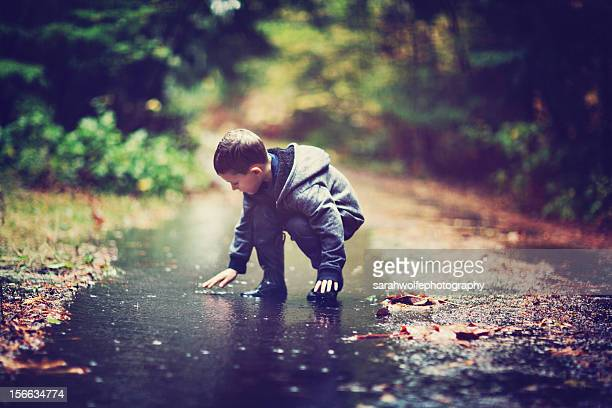 boy playing in a mud puddle