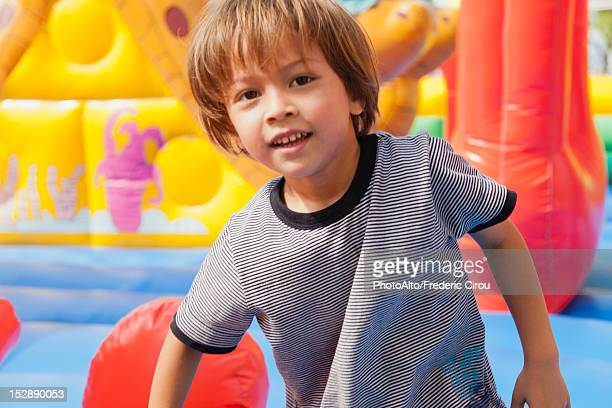 Boy playing in bouncy castle, portrait
