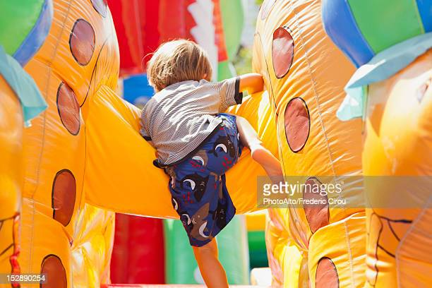 Boy playing in bouncy castle, rear view