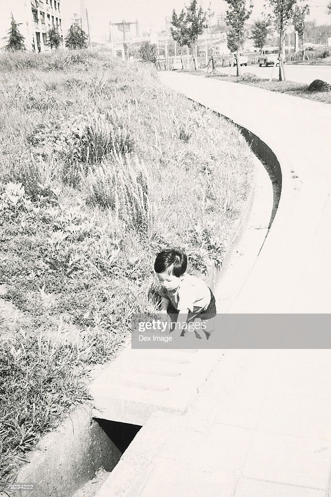 Boy playing in drainage : Stock Photo