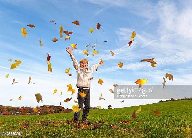 秋の葉で遊ぶ少年