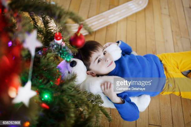 A boy playing in front of the Christmas tree