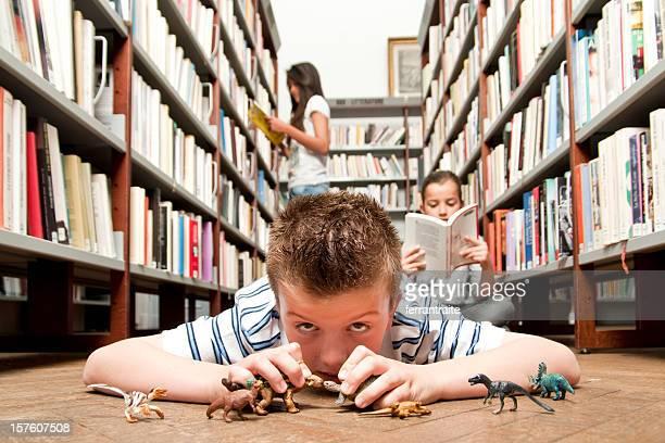 Junge spielt in der Bibliothek