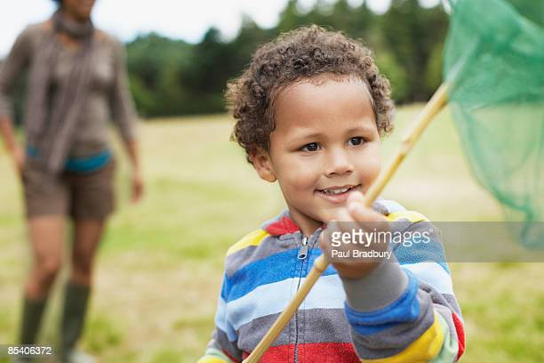 Boy playing in park with butterfly net