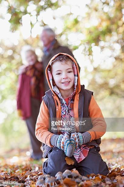 Junge spielt in Haufen Herbstblätter
