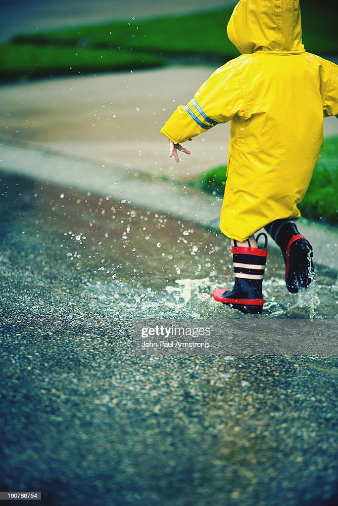 Boy playing in puddle water : Stock Photo