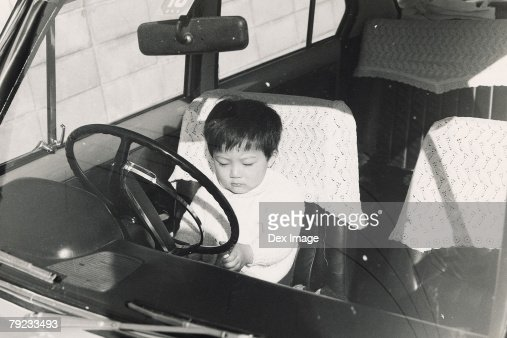 Boy playing in the driver's seat : Stock Photo