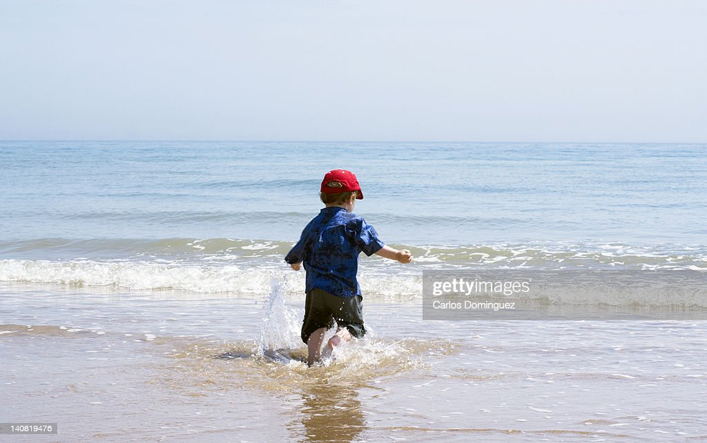 Boy playing in the sea : Stock Photo
