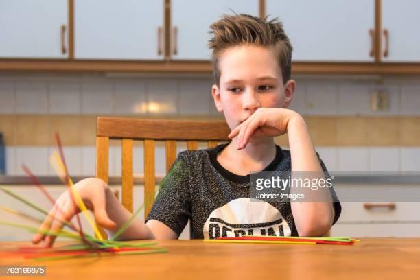 Boy playing jackstraws