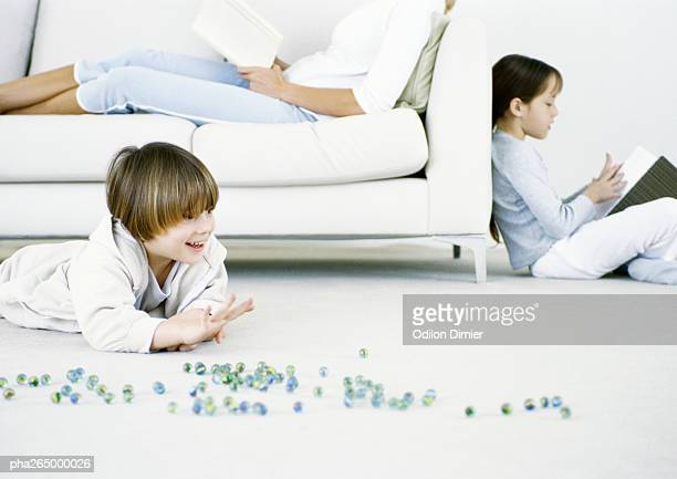 Boy playing marbles on floor, woman and girl reading in background