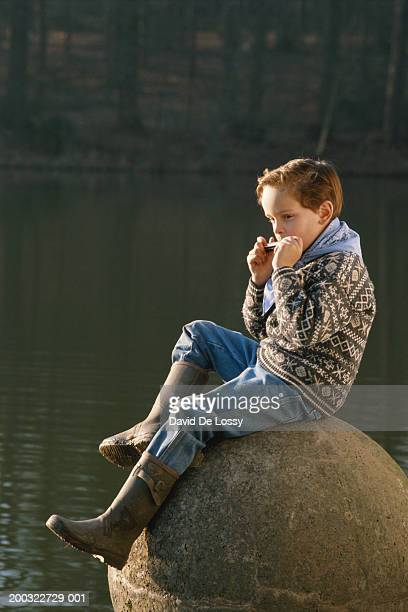 Boy (8-9) playing mouth organ, sitting on rock, side view