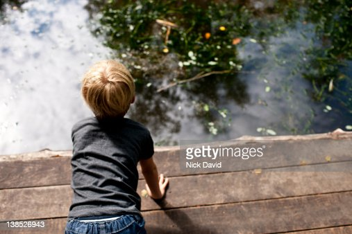 Boy playing next to water : Stock Photo