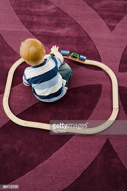 Boy playing on a carpet.