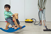 Boy Playing on a Rocking Horse and His Mother Vacuuming