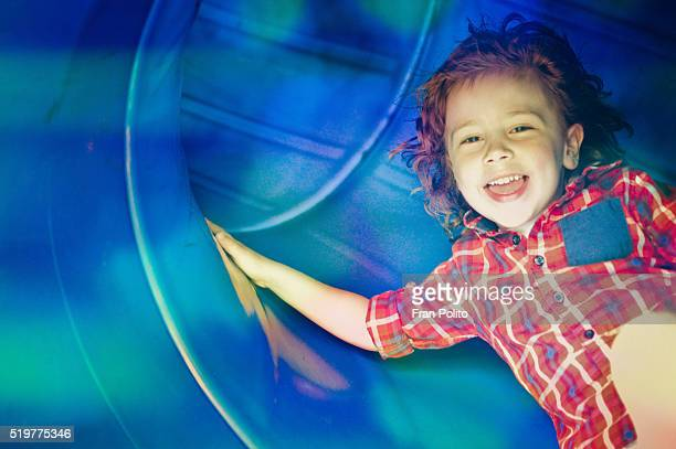 Boy playing on a slide at the park.