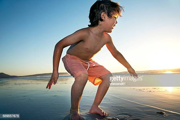 Boy playing on beach at sunset