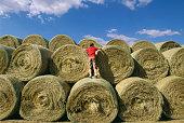Boy playing on cut hay rolls