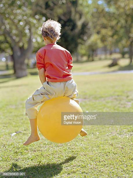 Boy (9-11) playing on inflatable hopper, rear view