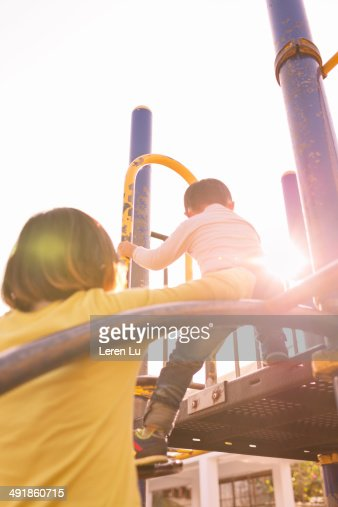 Boy playing on playground with mother. : Stock Photo