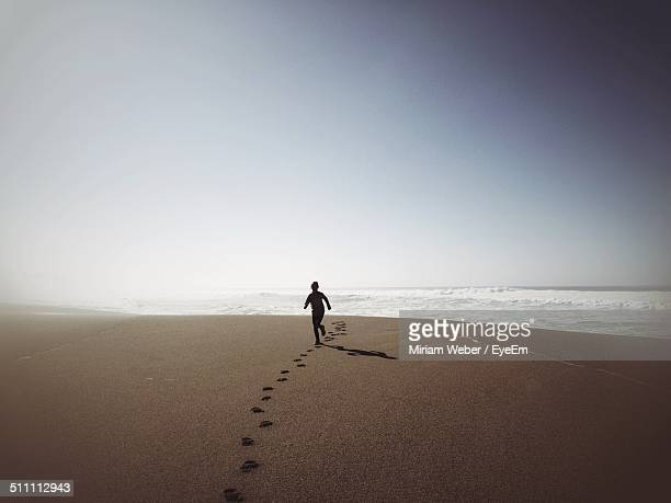 Boy playing on sand against clear sky