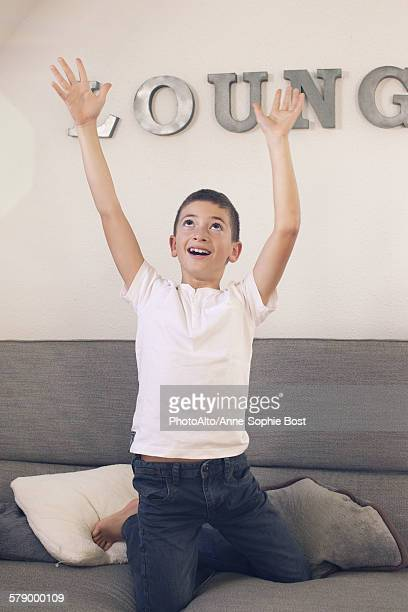 Boy playing on sofa with arms raised in the air