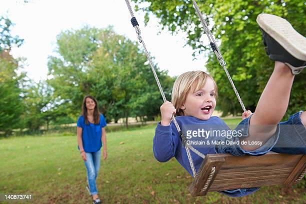 Boy playing on swing in backyard