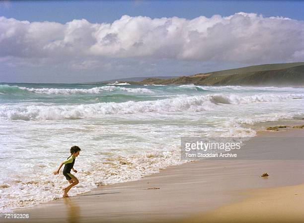 A boy playing on the beach at Indijup Point near Margaret River Western Australia