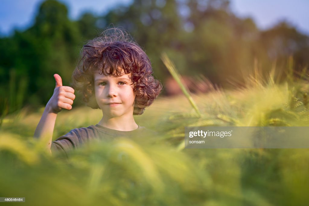 Boy playing on the filed in sunset, Thumbs up! : Stock Photo