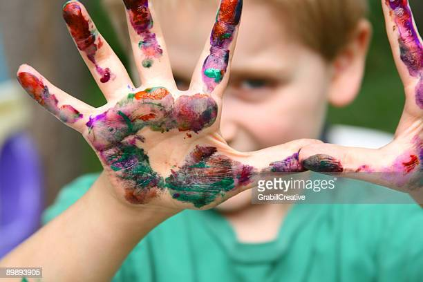 Boy Playing Peek-a-boo from behind paint-covered Hands
