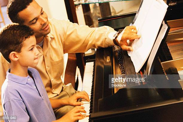 Boy playing piano while teacher pointing to sheet music