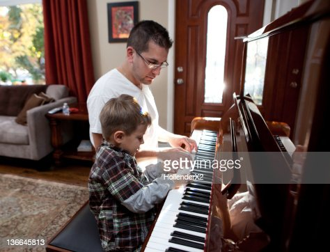 Boy playing piano with father